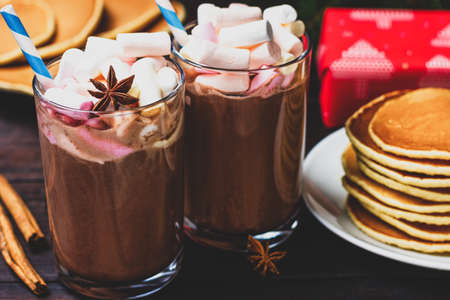 Two glasses of hot chocolate with marshmallows, anise star and pancakes on the background of New Years, Christmas padarka