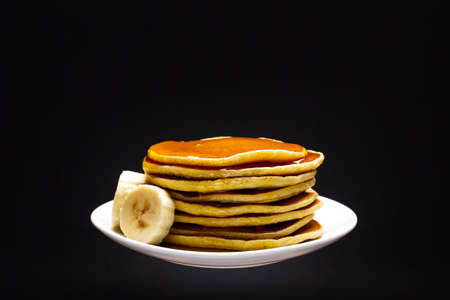 White plate on black background with pancakes and banana slices