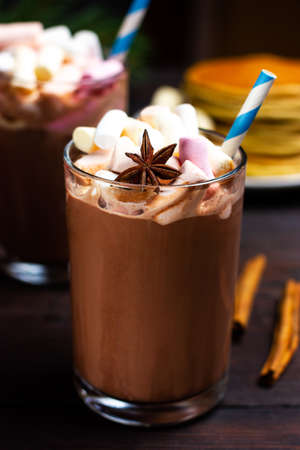 Hot chocolate or cocoa with colored marshmallows in a glass glass.