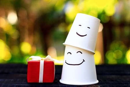 Two white cups with drawn emotions of joy and a red gift. Father and child symbol.