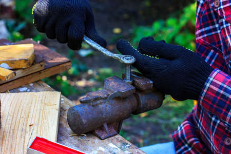 Grandpa works in a forest workshop. Grandpa tightens a nut on a bolt that is clamped in a vice