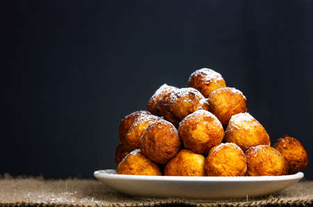 Festive homemade donuts for Hanukkah in rustic style on a dark background.