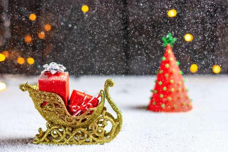 Santas sleigh with gifts, heavy snowfall and christmas tree. Christmas mood