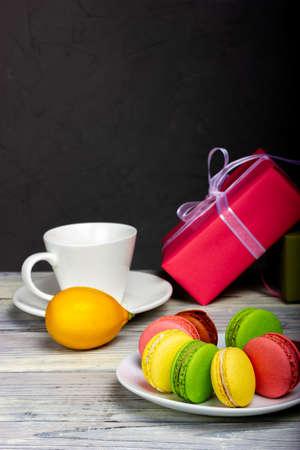色的蛋白杏仁饼干曲奇饼和礼物盒在黑暗的背景。