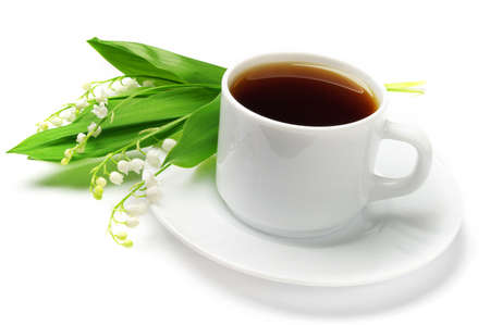Cup of tea and lilies of the valley on a white background photo