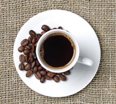 caffeine: Cup of coffee on a background fabric and coffee beans Stock Photo
