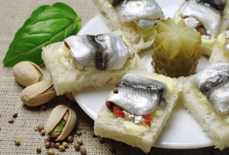 sprats: Sandwiches with sprat on a white plate