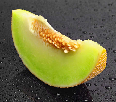 Melon slices on a background with drops closeup photo