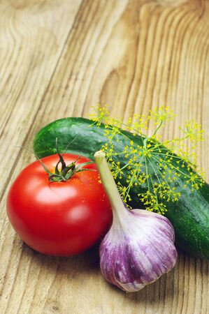 garnishing: Tomato, garlic and cucumber on wooden table