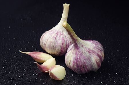 Two fresh garlic and cloves with water drops   Stock Photo