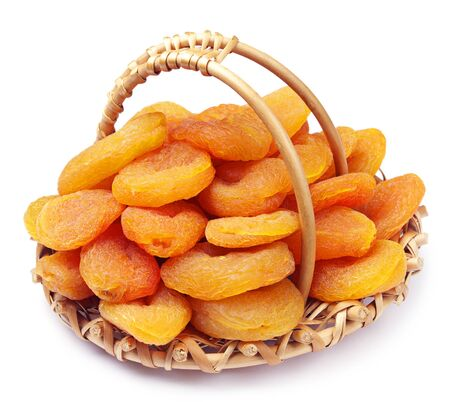 Dried apricots in a wicker basket on white Stock Photo