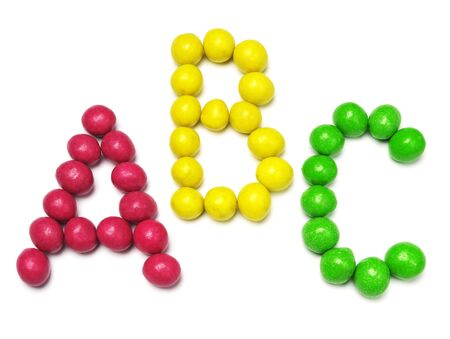studio b: Letters A, B and C from colored candy on white