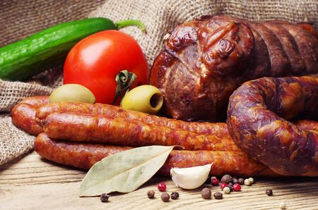 Smoked sausage, meat and vegetables on wooden table photo