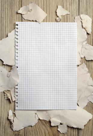 Hoja en blanco del cuaderno en el fondo de un papel rasgado en una mesa de madera