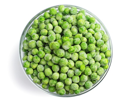Green frozen peas in a glass bowl on white. Top view