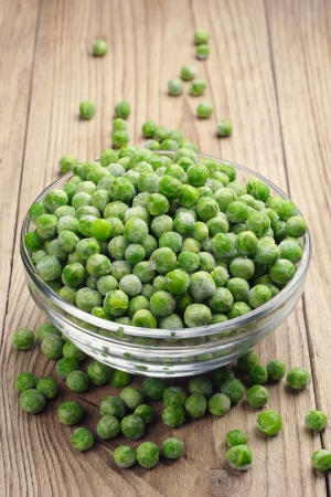 Frozen peas in a glass bowl on a wooden table Stock Photo