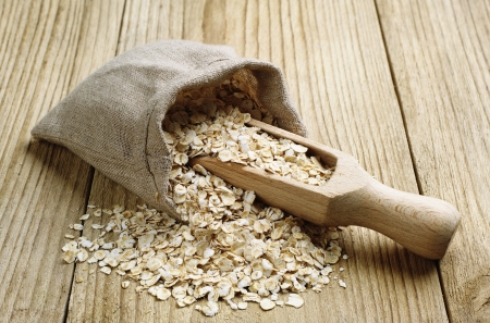 Oat flake in a sack and spoon on the wooden table