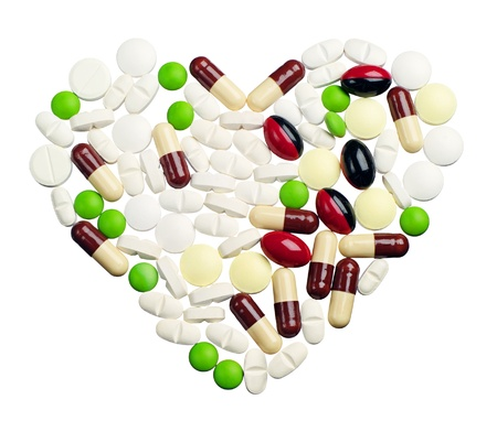 Different pills in the shape of a heart isolated on white photo