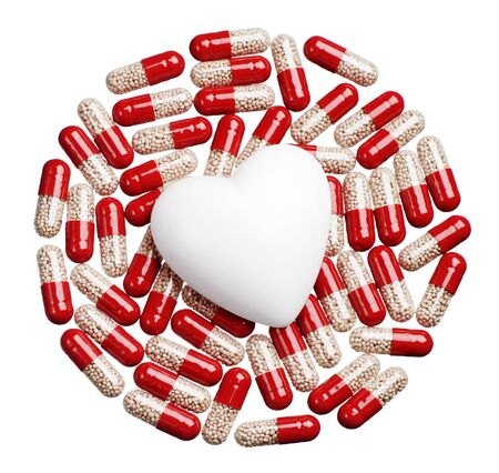 Capsule pills and heart isolated on white photo