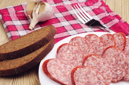 Smoked sausage sliced and bread on wooden table photo