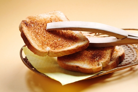 Wooden tongs and slice toast on a yellow background Stock Photo