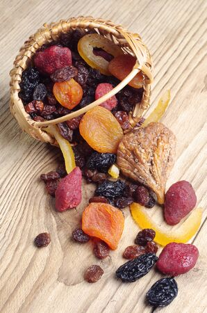 Dried fruits in a wicker basket and near on a wooden table photo