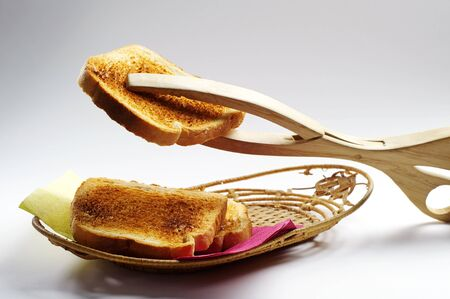 Toast and wooden tongs for bread