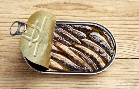 Sprat with oil in an open tin can on a wooden table Stok Fotoğraf