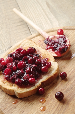 One toast with cranberry jam on wooden table Stok Fotoğraf