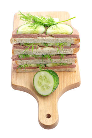Sandwiches with liverwurst and cucumber on a cutting board isolated on white photo