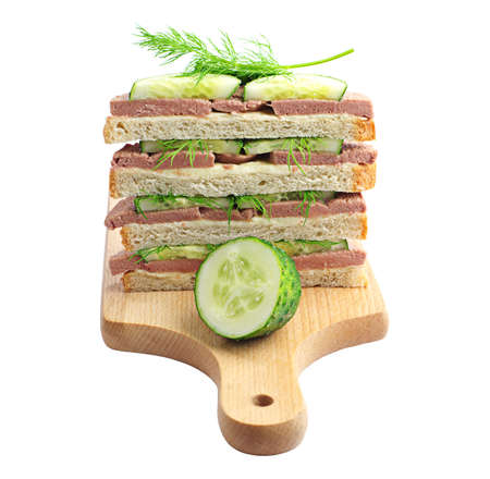 Sandwiches with liver sausage and cucumber on a cutting board isolated on white photo