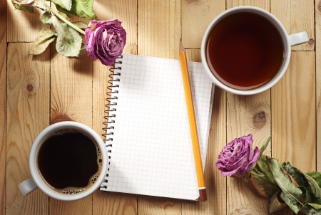 Cup of tea, coffee, dried roses and notebook on a wooden table photo