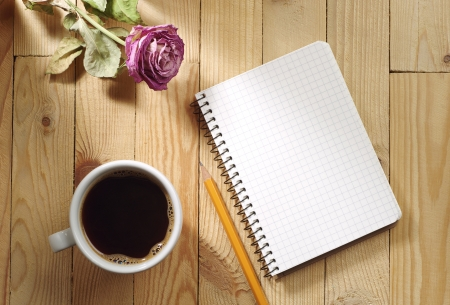 Cup of coffee, dried roses and notebook on a wooden table photo