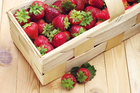 Strawberries in a basket and near on a wooden table photo
