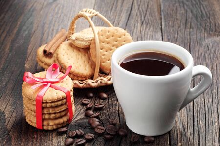 Cup of coffee and sweet cookies on a wooden table photo