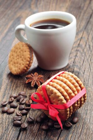 Cookies tied with red ribbon and cup of coffee on a wooden table photo