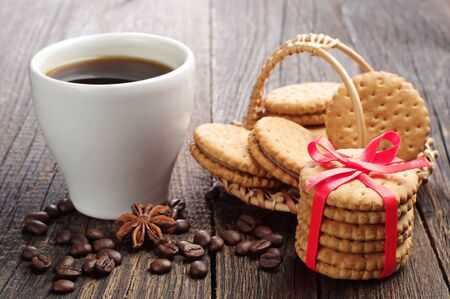 Sweet cookies tied ribbon and cup of coffee on a wooden table photo