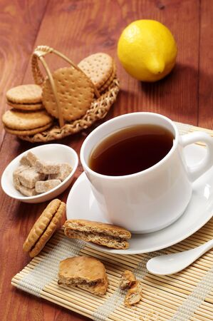 Cup of tea and sweet cookies on a wooden table photo