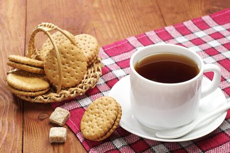 Cup of tea with biscuits on a wooden table photo