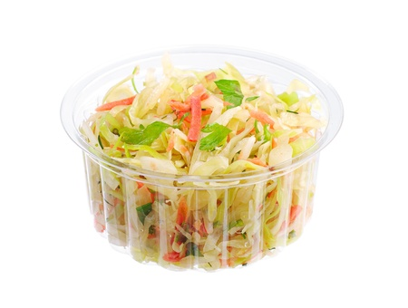 Coleslaw with carrot, onion and apple in a plastic packaging isolated on white