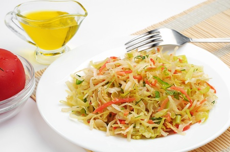Coleslaw with carrot, onion, apple and olive oil on table