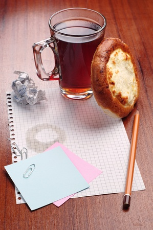 Notebook paper, pencil and a cup of tea with bun on the table photo