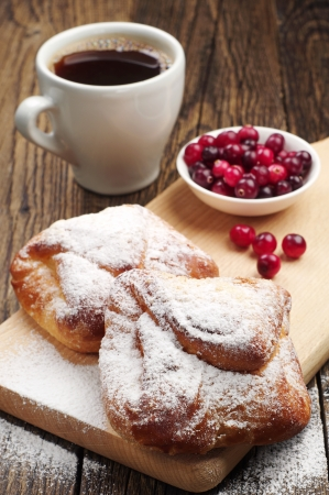 Sweet buns cup of coffee and cranberry on wooden table