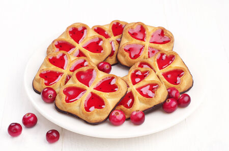 Sweet cookies with jam and cranberry on white table photo