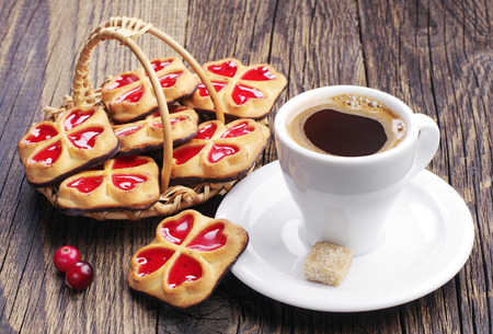 Cup of coffee and sweet cookies with jam and cranberry photo
