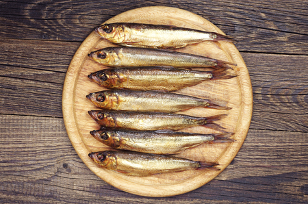 Smoked fish on a round cutting board on wooden table  Top view photo