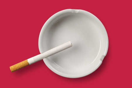 White ashtray and cigarette on red background. Top view