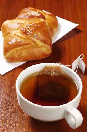 Cup of hot tea with teabag and sweet buns on table photo