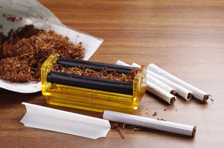 Rolling machine and cigarettes on brown table