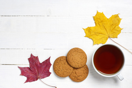 Cup of tea, biscuits and maple leaves on a white wooden table photo